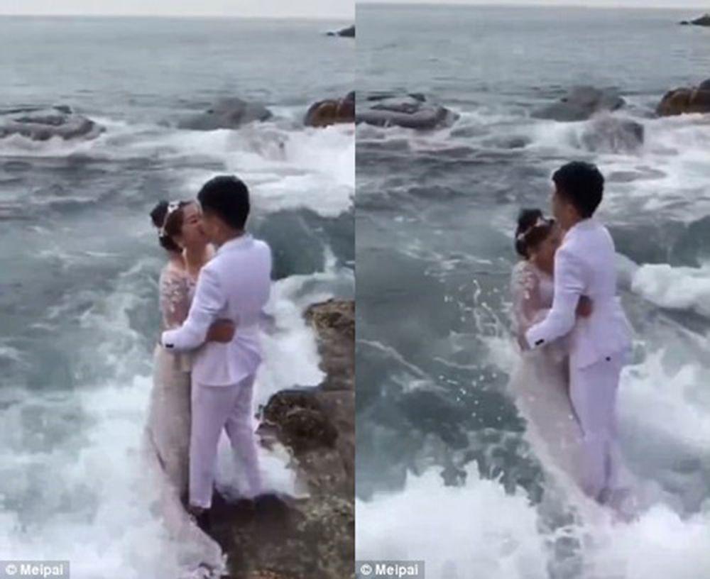 Video clip quay cảnh cô dâu chú rể mặc lễ phục cưới màu trắng đang đứng tạo hình trên một tảng đá ở bờ biển. Khi hai người sắp hôn nhau thì ...