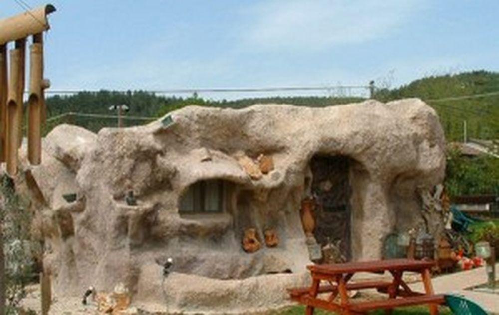 Căn nhà với thiết kế bên ngoài như những ngôi nhà thường thấy trong phim  thời tiền sử. Nhìn từ xa, bạn sẽ nghĩ ngôi nhà đang nằm ở trong một hang ...