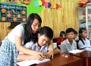 Cô giáo trẻ làm điểm tựa cho trẻ khuyết tật