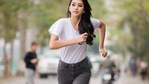 Hoa hậu Tiểu Vy mặc áo phông trắng, quần jeans, bụng bẳng lì để chạy bộ
