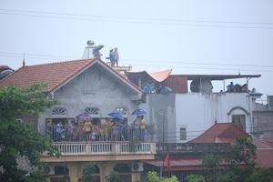 Hà Nội: Người dân đội mưa, trèo nóc nhà xem trai bơi trổ tài sông nước