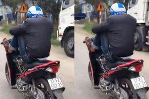 Nam thanh niên dùng chân lái xe máy, tay nghịch điện thoại khi đi xe trên quốc lộ