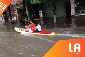 Mưa ngập qua đầu gối, người dân đem ván ra đường 'lướt sóng'