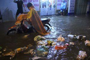 Người Hà Nội dầm mưa, bì bõm rẽ 'biển nước' ngập rác để về nhà