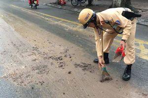 Cảnh sát giao thông dọn bùn đất trên đường, giúp xe lưu thông ở Hà Nội