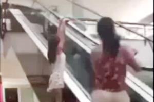 'Hãi hùng' bé gái nghịch dại với thang cuốn
