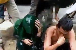 Cặp đôi bị tố ngoại tình ngồi im để dân làng dội nước cống lên đầu