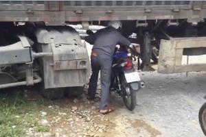 Container bị mắc kẹt chắn ngang quốc lộ, nhiều xe máy chui qua gầm bất chấp nguy hiểm