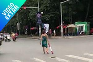 Người phụ nữ 'kỳ lạ' cầm gậy, đứng giữa giao lộ chờ xe