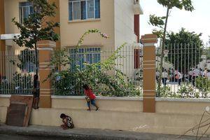 Hình ảnh khiến mọi người suy ngẫm:3 em nhỏ bán vé số bám hàng rào xem khai giảng