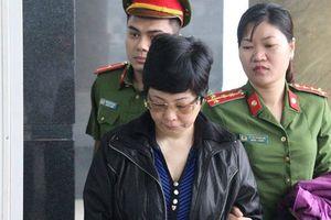 Bà Châu Thị Thu Nga mặc áo khoác đen, né ống kính phóng viên ra tòa phúc thẩm