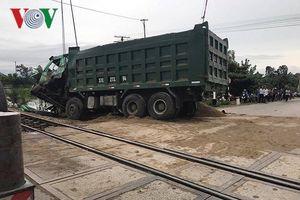 Tàu hỏa tông nát đầu xe tải chở cát