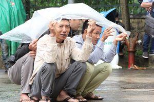 Người dân mặc áo mưa theo dõi phiên xử Đặng Văn Hiến