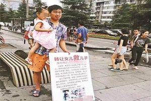 Người cha gây phẫn nộ khi cầm biển rao bán con gái để có tiền chữa bệnh cho con trai