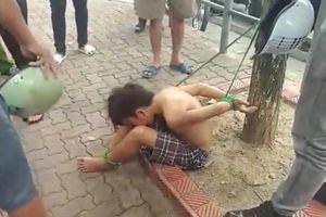 Cậu bé đánh giày cởi trần bị trói hai chân hai tay vào gốc cây gây xôn xao