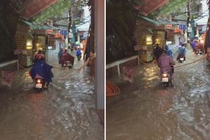 Người phụ nữ đứng trên phố ngập nước, cầm gậy đánh người đi đường