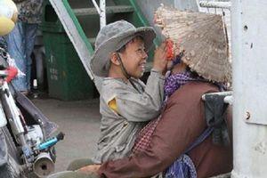 Bức ảnh 'nụ cười vô tư của cậu bé ăn xin và hành động vuốt má người mẹ đầy trìu mến' khiến bao người cảm thấy ấm lòng