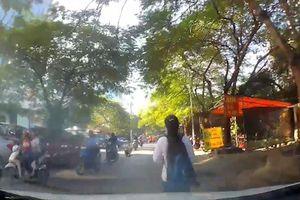 Đi bộ cản đường ôtô, cô gái suýt vấp ngã