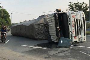 Tài xế bị thương bò ra khỏi xe container lật nhào