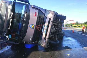 Ô tô tải lật, 120 thùng axit rơi xuống đường 'bốc khói'