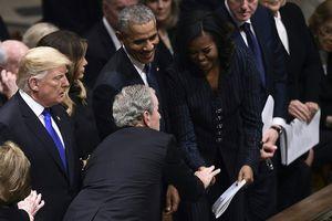 Cựu Tổng thống George W. Bush dúi kẹo vào tay bà Michelle Obama trong tang lễ của cha