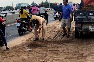 CSGT cùng người dân dọn cát rơi trên đường