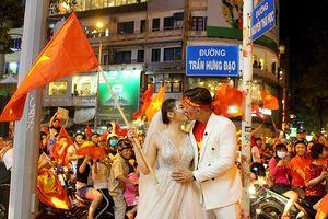 Cô dâu chú rể chụp ảnh cưới giữa 'bão' Việt Nam vô địch