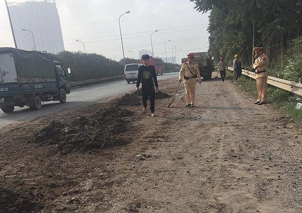 Cảnh sát giao thông Hà Nội quét dọn đất cát rơi trên Đại lộ Thăng Long