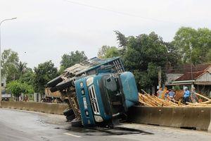 Xe tải chở gỗ lật, đè hai vợ chồng bị thương nặng