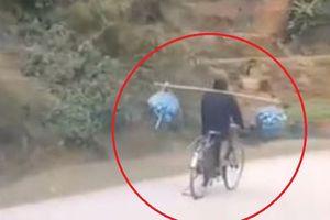 Người đi xe đạp giữ thăng bằng và gánh hàng hóa khi đang chạy
