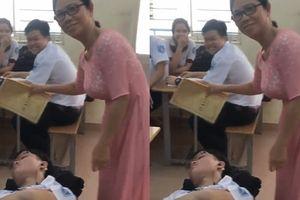 Nam sinh nằm sõng soài ngủ trên ghế trong giờ học, cô giáo không phạt lại xuống tận nơi chăm sóc tận tình