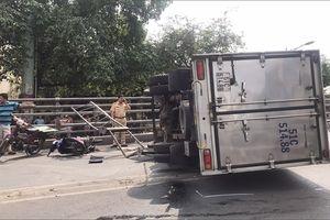 Xe tải lật trên cầu vượt Cây Gõ, hai người đi xe máy bị thương nặng