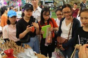 Du khách thích thú với sản phẩm handmade ở chợ phiên Hội An