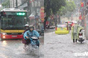 Ô tô phải bật đèn chiếu sáng, người đi xe máy xuống dắt bộ trong trận mưa lớn ở Hà Nội