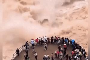 Du khách liều mạng đứng xem dòng nước dữ ở Trung Quốc