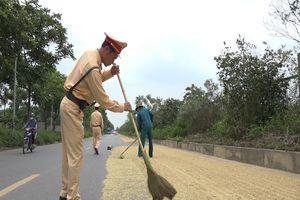 Cảnh sát giao thông nhắc nhở việc phơi thóc trên đường ở Hà Nội