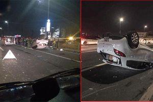 Xe Mazda lộn nhiều vòng rồi lật ngửa trên cầu Nhật Tân, nữ tài xế nguy kịch