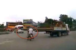 Rùng mình clip tài xế chở gỗ dài gấp đôi ô tô tải đập trúng đầu người đi xe máy