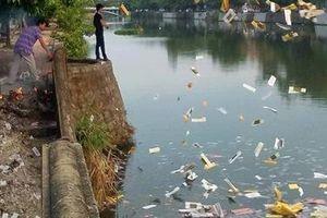 Hai người đàn ông rải vàng mã xuống sông Đông Ba gây ô nhiễm