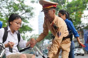 Cảnh sát giao thông giúp thí sinh ngồi xe lăn vào phòng thi