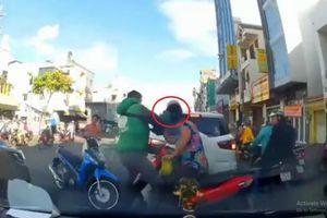 Nam thanh niên mặc trang phục Grap dùng mũ bảo hiểm phang thẳng đầu phụ nữ