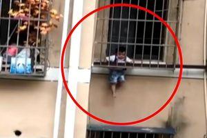 Bé trai ở nhà một mình lủng lẳng giữa các song sắt cửa sổ tầng 3
