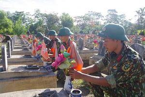 Cán bộ, chiến sĩ Sư đoàn 324 chăm sóc các ngôi mộ ở Nghĩa trang Liệt sĩ Việt - Lào
