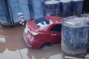'Xế hộp' kẹt dưới mương nước sau cú đánh lái tránh cụ bà