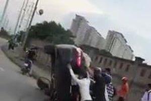 Đám đông hợp sức cứu tài xế lái ôtô lật ngửa giữa đường
