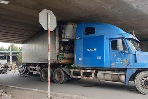 Chạy vào đường cấm, xe container mắc kẹt dưới gầm cầu vượt