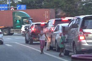 Cảnh trẻ đeo bám du khách, vịn cửa ô tô ăn xin ở TP.HCM