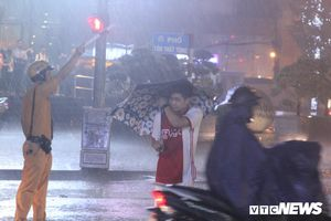 Cảnh sát giao thông dầm mình dưới mưa lớn điều tiết giao thông hỗn loạn ở Hà Nội