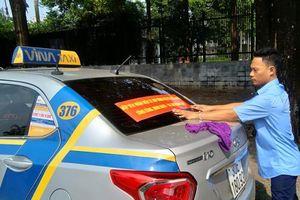 Tài xế taxi truyền thống dán băng rôn ủng hộ việc gắn mào trên xe taxi công nghệ