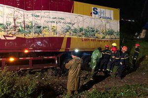 Sau tai nạn, cả tài xế và xe máy bị cuộn trong gầm container